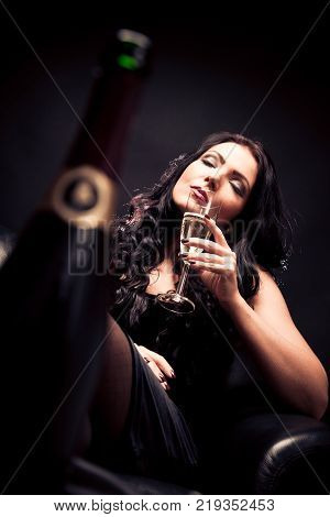 young woman enjoying a glass of champagne. selective focus with champagne bottle in the foreground.