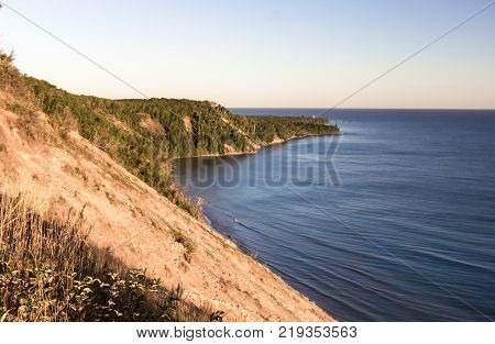Lake Superior Coast. Massive sand dune towers above the blue water of Lake Superior in the Pictured Rocks National Lakeshore in Grand Marais, Michigan, USA.