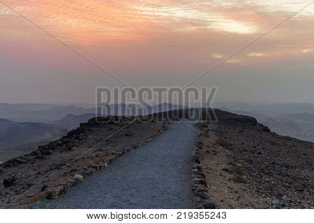 Sunrise in negev desert in israel. Mountain road to colorful horizon view. Tourism in national park valley with stones, rocks, sand beautiful red sun