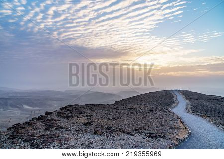 Colorful landscape view on judean desert land with magic sky on background and color clouds. Beautiful nature with mountains, rocks, sand and ruins in holy land in Israel.