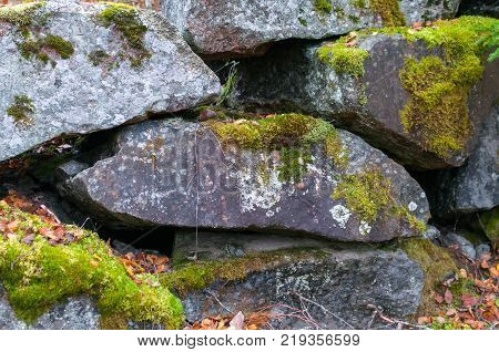 a wall of granite boulders covered with moss