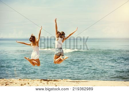 Travel concept with two happy girls jumping at hot sunny beach