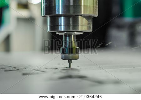 Spindle with a milling cutter inserted into the collet. Milling a part. You see small swarf from the milling.