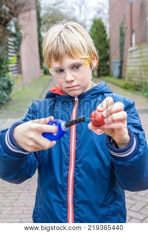 The Hague the Netherlands - 23 December 2017: blonde boy with safety glasses lighting fireworks