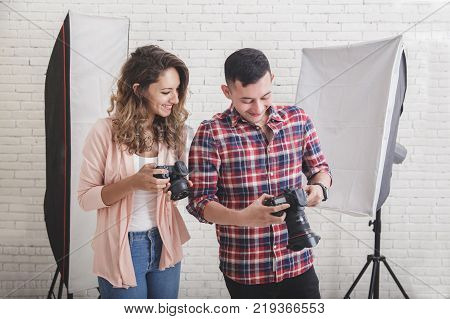 portrait of young photographer checking photo preview in his camera share with his partner in studio