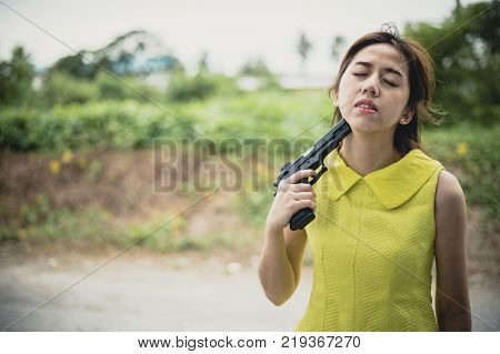 Stressed woman with holding gun on her chin point to her head.She is saddened by the disappointment in love. concept of broken heart, heartbroken, lovelorn, Suicide.