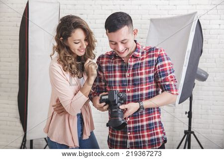 portrait of photographer viewing the photo preview in his camera to his model during photo session in studio