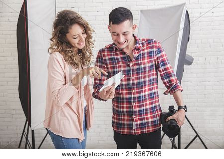 portrait of photographer sharing the result of his photo print to his model in studio