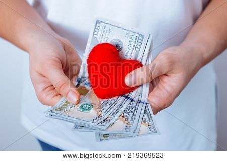 love or money concept hands hold heart and money in hands