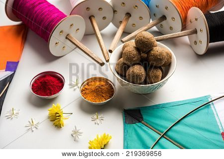 happy Makar Sankranti greeting card - Tilgul or Til ladoo in a bowl or plate with haldi kumkum and flowers with Fikri /Reel/Chakri /Spool with colourful thread or manjha and kite over plain background