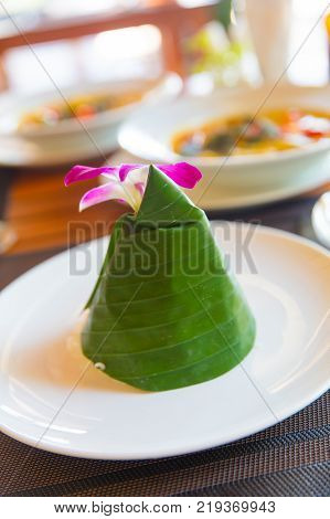 Closeup of steam rice wrapped in cone shape banana leaf with orchid flower served in Aonang Krabi Thailand