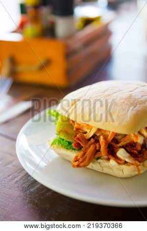 Closeup of fresh pulled pork burger served on table in restaurant