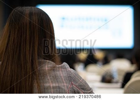 Back of businesswomen sitting and training in hall or meeting room with whie big screen background