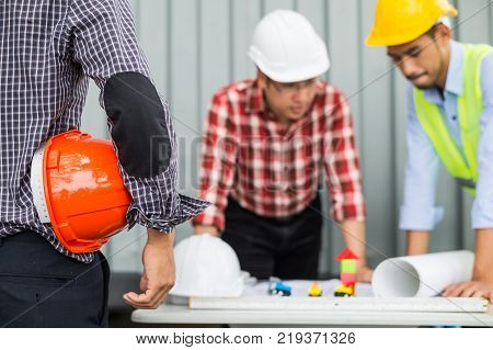engineer and construction team wearing safety helmet and working by checking progress of construction in blueprint reviewing material and checking construction process at construction site area.