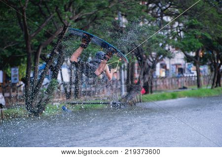 Fantastic image of A man practiced jumping his wakeboard on air and water splash at the lake. water sport at extreme park