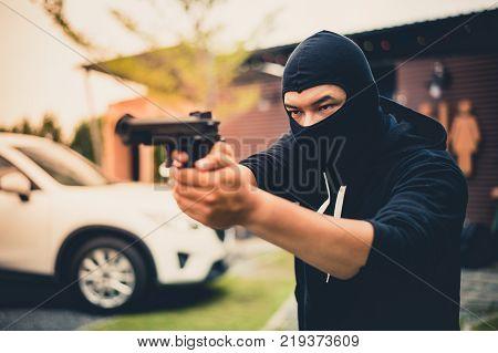 Picture of Criminal or Bandit wear black mask useing gun point to somewhere concept of criminal bandit gangster mafia