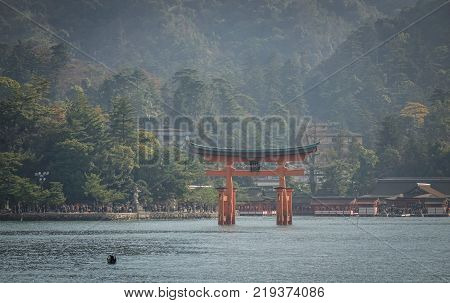 Hiroshima Japan - Dec 28 2015. Giant Torii of Itsukushima Shrine with cityscape background in Hiroshima Japan. The historic shrine is listed as a UNESCO World Heritage Site.