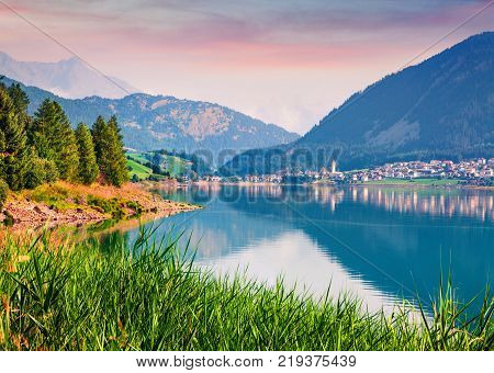 Splendidt summer sunrise on Resia (Reschensee) lake. Resia village in the morning mist Province of Bolzano - South Tyro Italy Europe. Artistic style post processed photo.