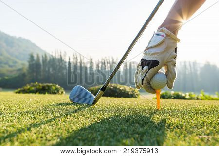 Hand hold golf ball with tee on course tee off
