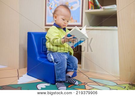 Cute little Asian 18 months / 1 year old baby boy child sitting on chair reading and turning the page of a book / storybook kid wearing sweater jeans baby socks Child development & education concept