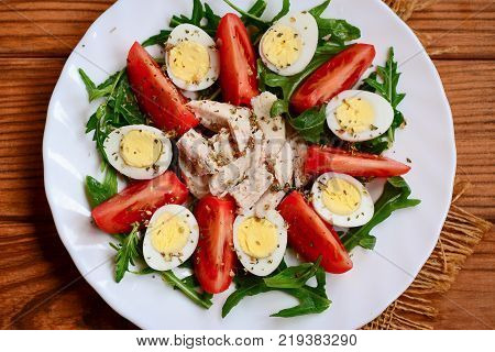 Fresh vegetable salad with boiled chicken breast and quail eggs. Salad with fresh tomatoes, rucola, quail eggs, chicken breast and spices on a serving plate and a wooden background. Closeup. Top view