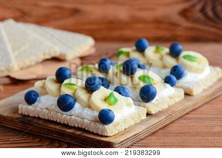 Crispbreads with cottage cheese, banana and berries on wooden board. Cottage cheese open sandwich photo. Closeup