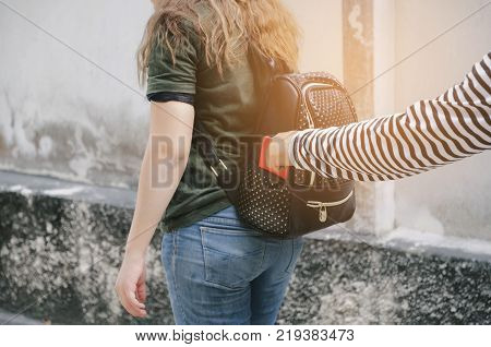 thief stealing the wallet or mobile phone from behind young caucasian woman bag on street thief crime robber and steal concept