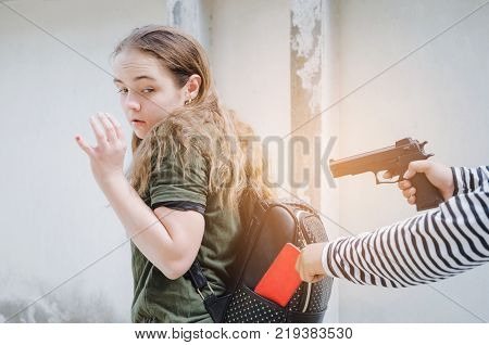 thief using the gun for stealing the wallet or mobile phone from behind young caucasian woman bag on street thief crime robber and steal concept