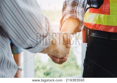 engineers and technician contractor shaking hands after finishing up a business meeting to greeting start up project contract in construction site building successful partnership teamwork concept