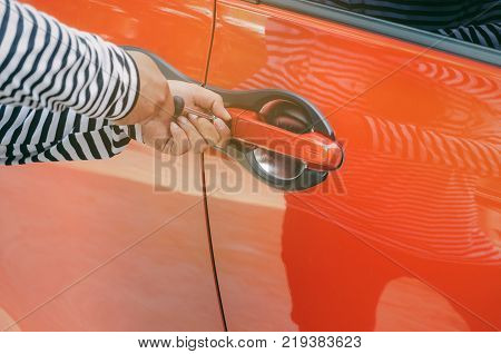 close up of hand thief in black and white jacket using screwdriver to open car door to stealing a car break into the car crime robber and steal concept