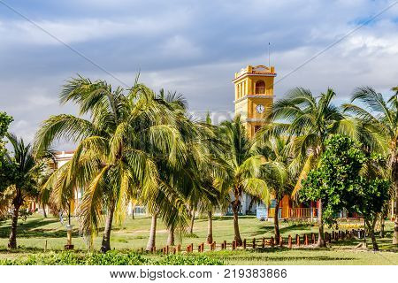 Yellow clock tower with palms at the front close to Ancon beach Trinidad Cuba