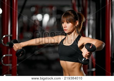 Young fitness girl standing in the gym holding dumbbells in a shoulder press position