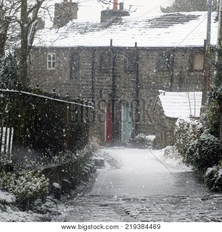 the village of heptonstall in snowfall showing ancient houses and small lane