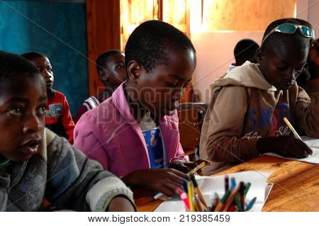 25 October 2017-Franciscan Center of Pomerini-Tanzania-Africa-A group of unidentified African children follow the after-school lessons helped by some unidentified members of a non-profit association