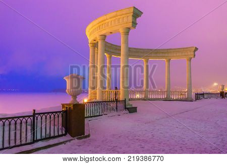 Rotunda on the embankment and a beautiful view of the frozen Izhevsky pond in the winter in the evening before sunset. Russia.
