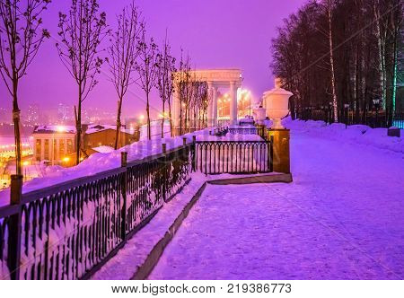 Rotunda parapet and trees on the embankment of the Izhevsk pond in Russia in the evening in the winter before sunset