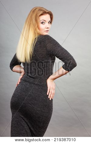 Woman wearing tight black dress showing her feminine body shape back view.