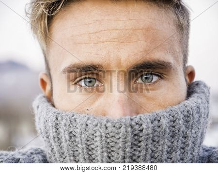 Headshot of handsome young man outdoor in winter fashion, wearing turtleneck sweater in snow environment