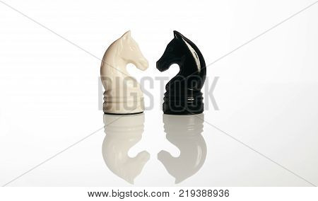 Close up of two black and white chess knight pieces on chessboard isolated on white background. Board game, business and planning concept.