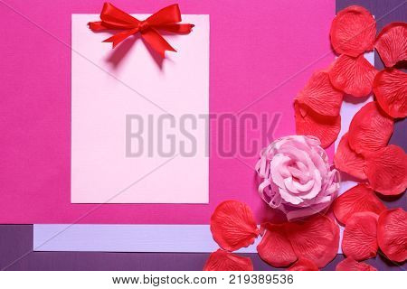 Blank paper note with bow and petals - Unwritten message card tied with red bow surrounded by a pink rose and red petals made of soap on magenta and purple paper backgrounds.