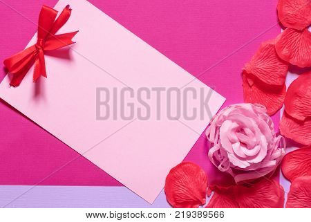 Message card with bow and rose petals - Pink paper note with a red tied bow surrounded by soap rose and petals on a magenta paper background. Greeting card idea for birthdays and events.