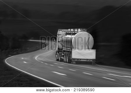 Tanker truck in motion - Black and white image with tanker truck driving on a countryside road outside the german city Schwabisch Hall Baden Wurttemberg Germany