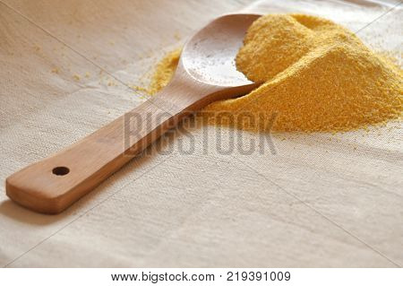 Pile of organic corn grits and a wooden spoon on coarse cloth. Prepared ingredient for cooking. Image with copy space.