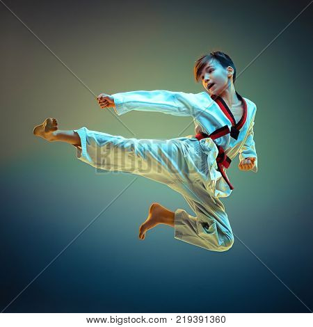 Young boy training karate and jumping on blue studio background