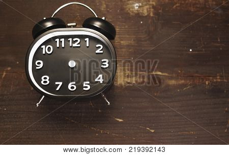 a black and white vintage alarm clock laying on a wooden background
