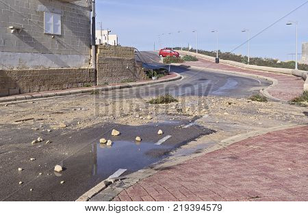 XGHAJRA MALTA - DECEMBER 22 2017: Consequences and Destruction of the road and stones after a storm and strong waves Malta