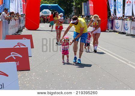 ODESSA UKRAINE - 25 JUN 2017: Parents and children at marathon. Happy kid runners at finish line at summer maraton.