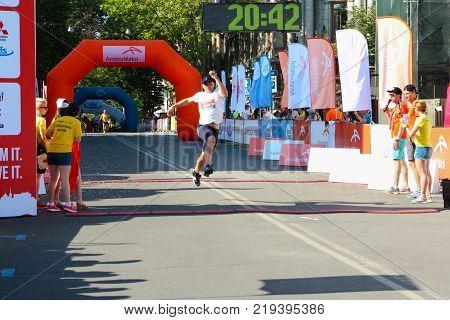 ODESSA UKRAINE - 25 JUN 2017: Excited runner crossing the finshline of a marathon. Marathon athlete at finish. Happy marathon runner finish line.