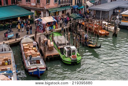 Venice, Italy - October 13, 2017: pier on the Grand Canal. Designed for cargo boats. cargo boats. Boats and gondolas are moored. On the embankment there is a souvenir tent.