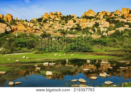 Beautiful nature scenery with bright blue lake against the background of blue sky and strange landscape with large rocks, Hampi, India